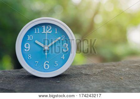 Blue alarm clock on stone with nature background close up blue alarm clock