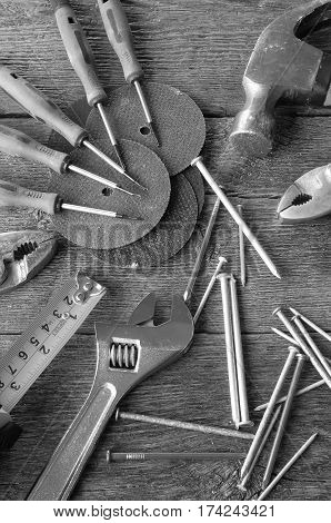 A top view image of various small hand tools on a wooden workbench.