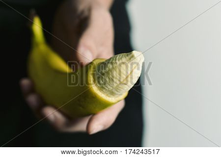 closeup of the hand of a young man with a banana with the tip of its skin removed, depicting a circumcised male member
