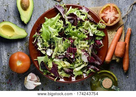 high-angle shot of a rustic wooden table with some ingredients to prepare a salad; a plate with lettuce mix, tomatoes, an avocado cut in half, some carrots and a cruet with olive oil