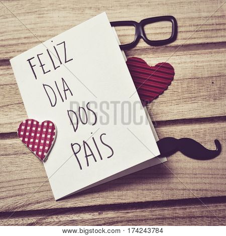 the text feliz dia dos pais, happy fathers day in Portuguese written in the page of a notebook, a pair of black eyeglasses, a mustache and some red hearts on a rustic wooden background