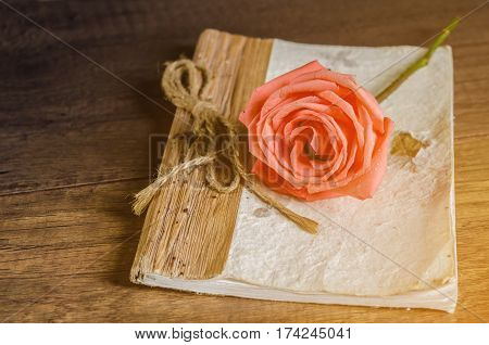 Beautiful rose and vintage diary on wooden background.