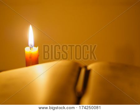old tattered book on a wooden table lighted candle