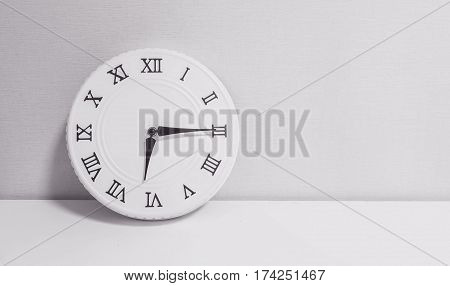 Closeup white clock for decorate show a quarter past six or 6:15 a.m. on white wood desk and wallpaper textured background in black and white tone with copy space