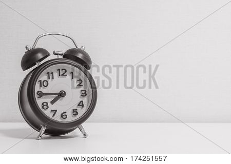 Closeup alarm clock for decorate show a quarter to eight p.m. or 7:45 a.m. on white wood desk and cream wallpaper textured background in black and white tone with copy space