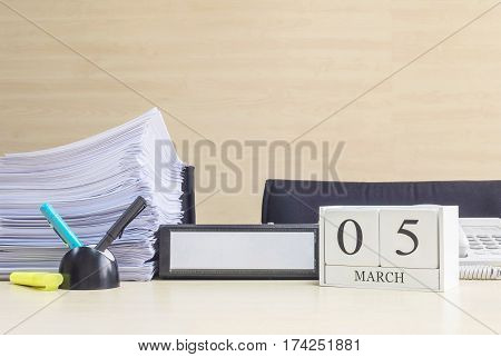 Closeup white wooden calendar with black 5 march word on blurred brown wood desk and wood wall textured background in office room view with copy space selective focus at the calendar