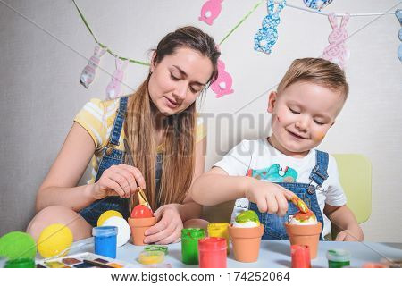 smilling boy making bunny for easter painting eggs