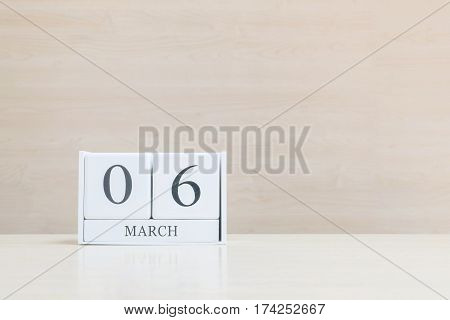 Closeup surface white wooden calendar with black 6 march word on blurred brown wood desk and wood wall textured background with copy space selective focus at the calendar