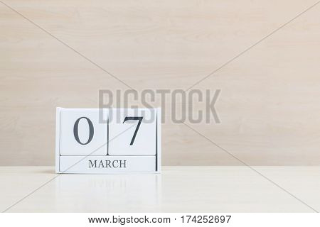 Closeup surface white wooden calendar with black 7 march word on blurred brown wood desk and wood wall textured background with copy space selective focus at the calendar