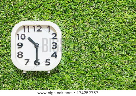 Closeup white clock for decorate show a half past ten or 10:30 a.m. on green artificial grass floor textured background with copy space