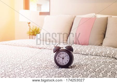 Close Up Of Alarm Clock On Bed With Sunlight In Bedroom