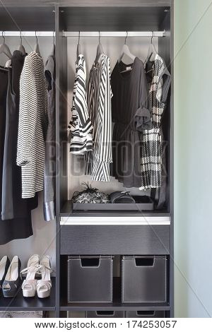Modern Closet With Row Of Black Dress And Shoes In Wardrobe.