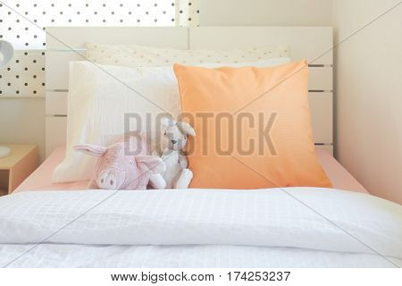 Piggy And Rabbit Doll Setting On Bed Next To Orange Color Pillow In Cutie Style Bedroom