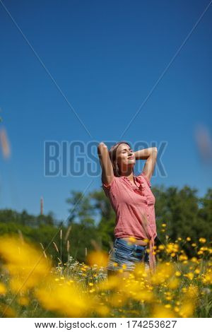 Woman enjoying summer at the field of flowers