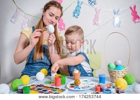 Mother teaches kid to do craft items for easter