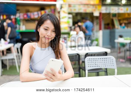 Woman sending sms on cellphone at outdoor restaurant