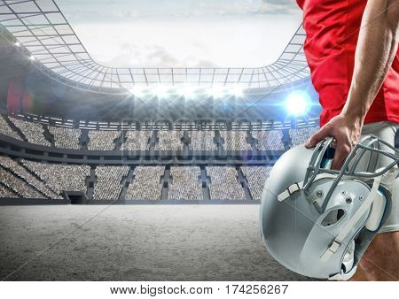 Mid-section of american football player standing with helmet against digitally composite stadium