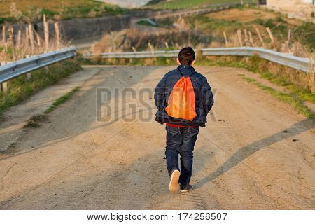 Teenager walking away on rough road. Concept of escape and adventure