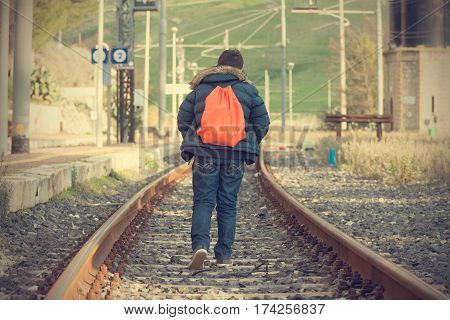 Teenager walking away on railway. Concept of escape and adventure poster