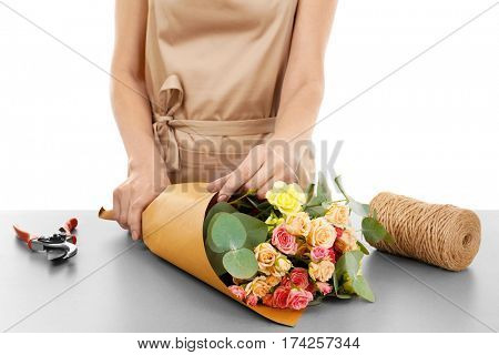 Female florist wrapping flower bouquet in paper on white background