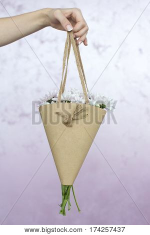 Crop photo of hand holding flowers in beige paper wrapper isolated on pink background.
