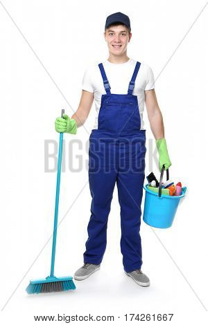 Young man holding cleaning equipment and supplies on white background