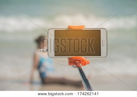 taking picture by smart phone selfie stick on blurred beautiful at beach background Vacation concept