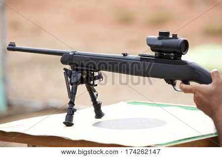 Rifle on the table are to be shot in a shooting gallery.