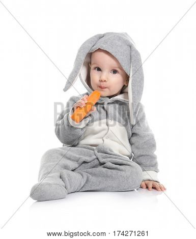 Cute little baby in bunny costume with carrot on white background