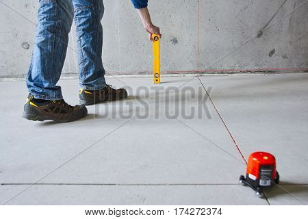 man with laser level check floor and walls