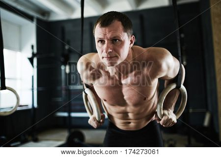 Intense workout in dark gym: mature male bodybuilder performing arm muscle endurance test on rings
