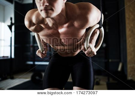 Intense workout in dark gym: closeup shot of male torso with bulging tense muscles at work during gymnastic rings exercise