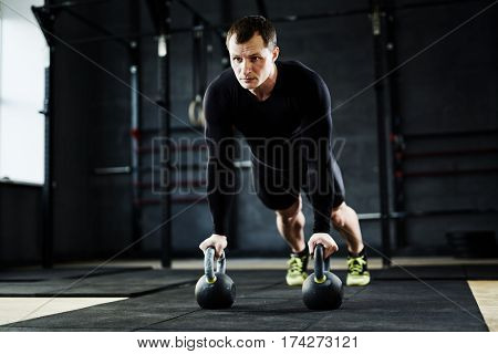 Intense workout in gym: male athlete performing kettlebell pushups looking determined and strained
