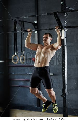 Young muscular male with big torso performing pull-ups at wall mounted bar during intense workout in gym, his torso and arm muscles strained and defined by lighting