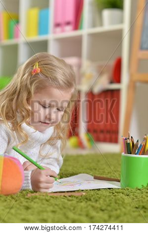 cute little girl drawing, lying on the floor