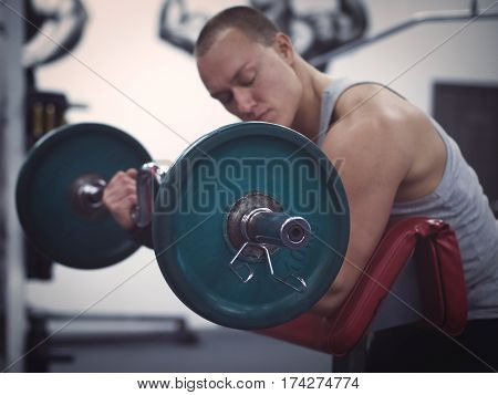 side view of muscular man holding barbell in gym. Focus on barbell. Training in gym concept. Toned image. Low key. Shallow DOF