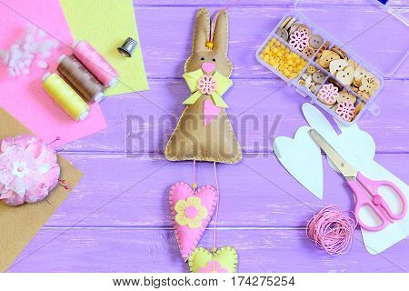 Cute felt Easter bunny with hearts decor. Craft supplies on a wooden background. Creative bunny wall decor. Handmade Easter crafts for children and adults to make. Top view
