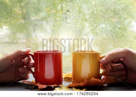 pair of hands holds hot drink in the colored mugs on the background window with raindrops / comfortable pastime together