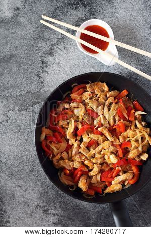 Fried pork with red peppers and piquant Asian sauce chopsticks. Top view