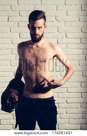 handsome bearded man or hipster guy dieting with bare slim or thin body chest and torso with anorexia holds purple shirt on white brick wall background