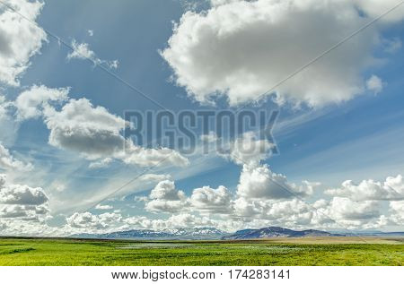 Open grassland with clouds and snow covered mountains. Beautiful landscape and cloudscape with blue sky in spring or summer. Colorful nature background. Green meadow. Iceland.