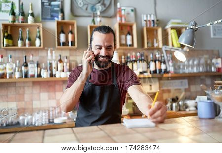 small business, communication, people and service concept - happy man or waiter in apron calling on smartphone at bar or coffee shop