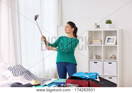 tourism, people and luggage concept - happy young woman packing travel bag at home or hotel room and taking picture with smartphone selfie stick