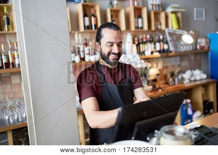 small business, people and service concept - happy man or waiter in apron at counter with cashbox working at bar or coffee shop