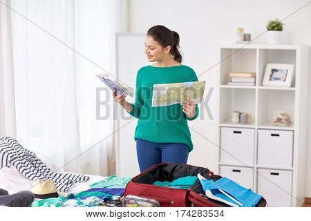 tourism, people and luggage concept - happy young woman with map and city guide packing travel bag at home or hotel room