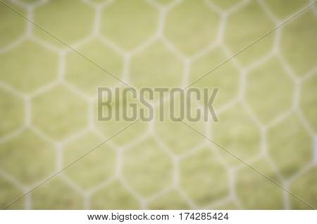 Blur soccer goal net blur white football net with green grass background.