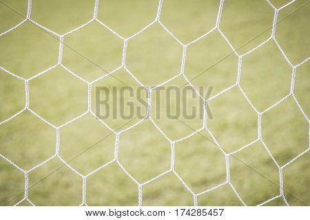 Soccer goal net white football net with green grass background.