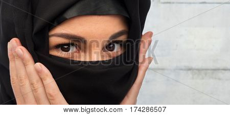 religious and people concept - close up of muslim woman in hijab over gray concrete wall background