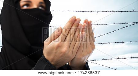 religion, faith, crime, imprisonment, islam and people concept - close up of praying muslim woman in hijab over barb wire background