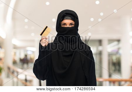 finances and people concept - muslim woman in hijab with credit card over shopping center background